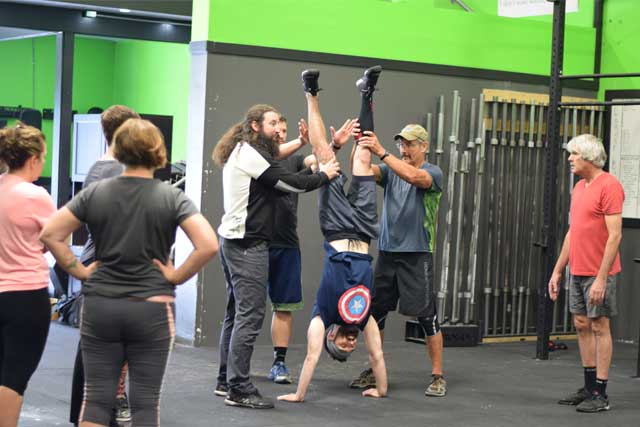 Jesse teaching a group about handstands