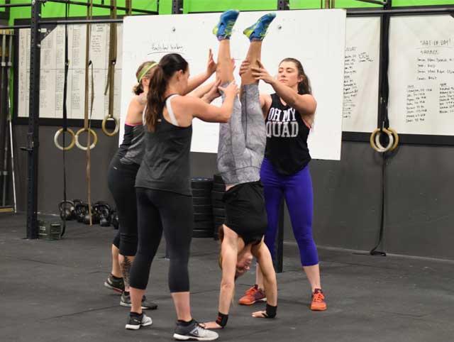Group of ladies practicing handstands