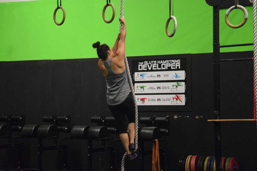 Back of woman doing a rope climb